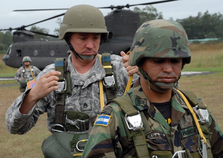 TAMARA DROP ZONE, Honduras - Army Staff Sgt. DavidHattan, Joint Task Force-Bravo Army Forces, checks the parachute of Capt.Erwin Lara, a TESON instructor with the Honduran army, prior to an airdrophere Dec. 8.  The air drop was the last requirement for the students in theTESON class.  TESON, which stands for Tropas Especiales para Operaciones deSelva y Nocturnas, is an elite Honduran unit akin to the U.S. Army Rangers.(U.S. Air Force photo by Tech. Sgt. Sonny Cohrs)
