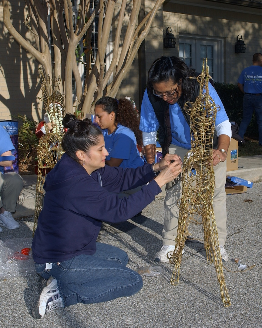 """Laura Sales and Jane Balderrama assemble a grapevine motion deer for the lawn of Fisher House II on Dec. 4. Employees from local San Antonio Wal-Mart and Sam's Club stores spent the day decorating the Lackland Air Force Base and Fort Sam Houston Fisher Houses. In addition to the decorations provided by """"Operation Deck the Walls,"""" each Fisher House received $5,000 in gift cards to buy items for the houses. (USAF photo by Alan Boedeker)"""