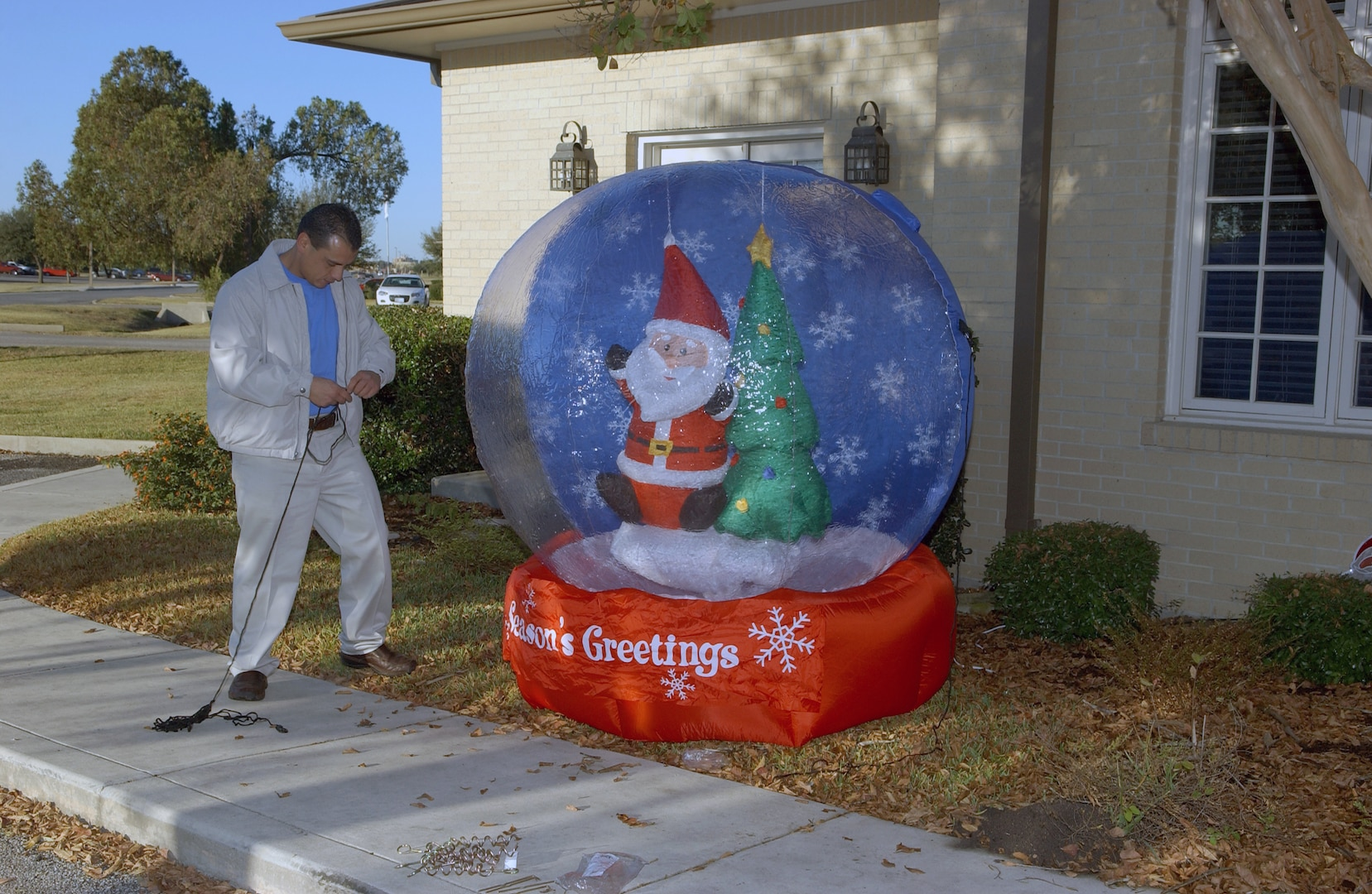 """Richard Mcumber finishes up a snow globe outside Fisher House II on Dec. 4. Employees from local San Antonio Wal-Mart and Sam's Club stores spent the day decorating the Lackland Air Force Base and Fort Sam Houston Fisher Houses. In addition to the decorations provided by """"Operation Deck the Walls,"""" each Fisher House received $5,000 in gift cards to buy items for the houses. (USAF photo by Alan Boedeker)"""