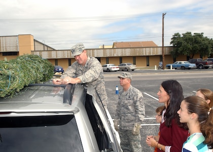 Stephanie Cooper and her children watch as Col. Eric Wilbur, 37th Training Wing vice commander at Lackland Air Force Base, Texas, secures a Christmas tree to their vehicle Dec. 6 at the Outdoor Recreation Center. An additional 40 trees were hand-delivered to families who have a deployed member. (USAF photo by Alan Boedeker)