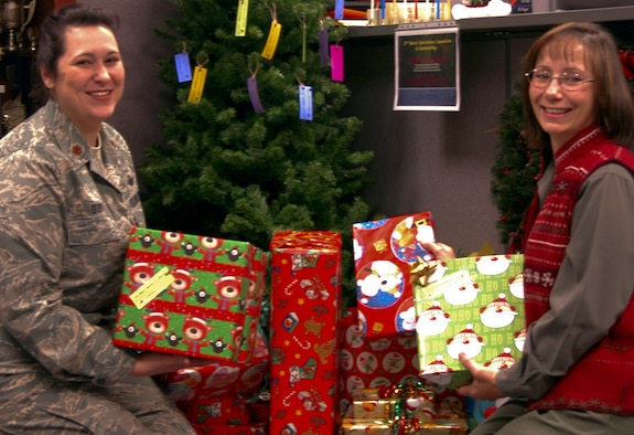 SCHRIEVER AIR FORCE BASE, Colo. -- Maj. Kristin Duby and Kristin Hunt place gifts under a tree as part of the Christmas for Kids toy drive here Dec. 4. Mrs. Hunt, secretary for the 2nd Space Operations Squadron, is spearheading the effort, which continues through Dec. 14. Major Duby is the Operations Flight commander for 2nd SOPS. (U.S. Air Force photo/Staff Sgt. Stacy D. Foster)