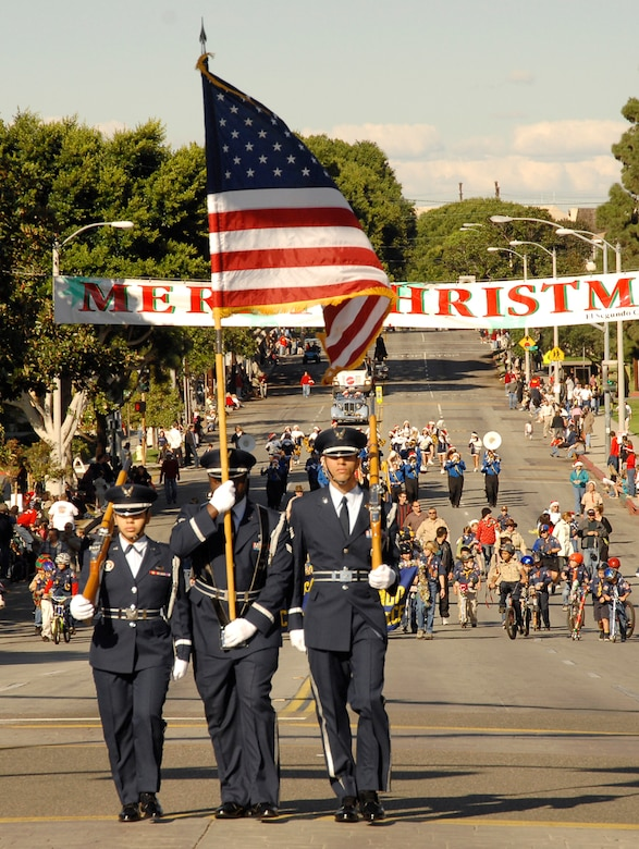 The Los Angeles Air Force Base Honor Guard kicked off this year's El Segundo Holiday parade, Dec. 9. Col. Joseph Schwarz, 61st Air Base Wing commander, and his wife Holly represented the base in the parade that also featured community leaders and school groups. (Photo by Lou Hernandez)