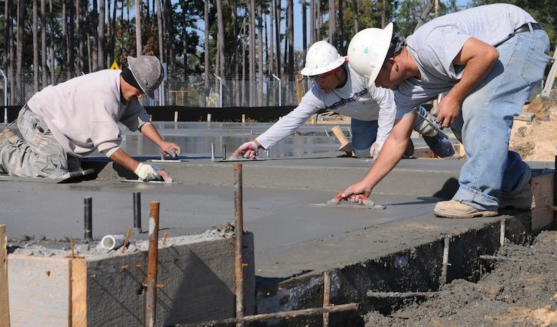 Concrete finishers Tobias Acostia, left, Alajondro Bonabadis and Octabio  Rodriguez finish a slab in Northwest Falcon Park.  (U.S. Air Force photo by Kemberly Groue)