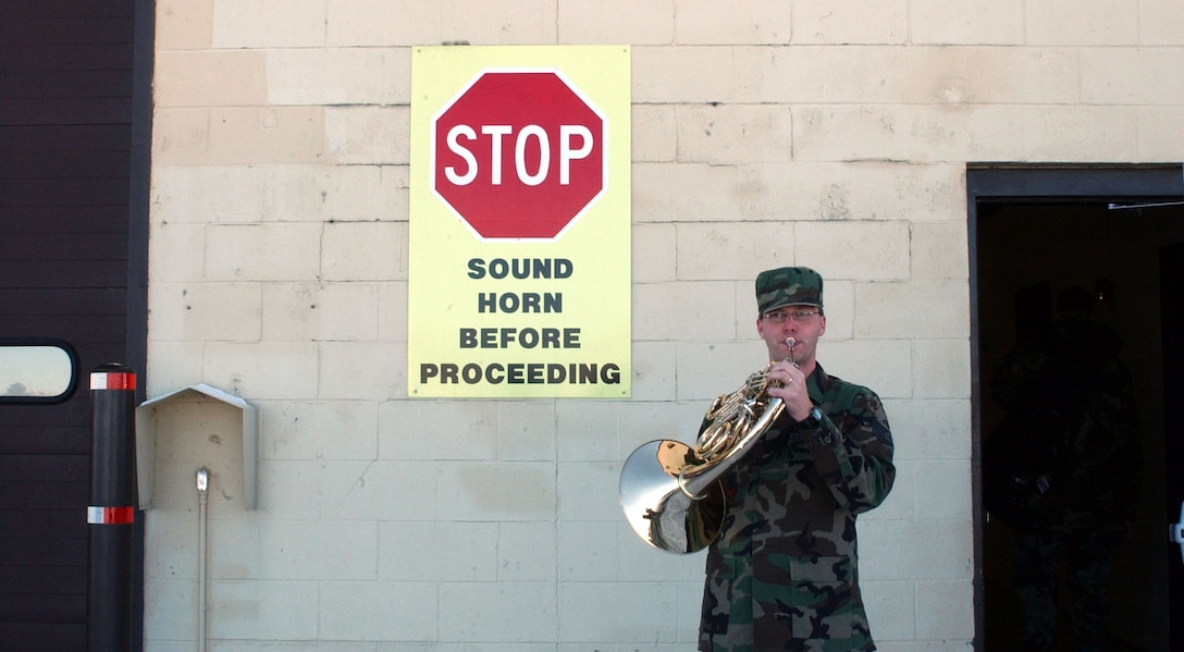 Staff Sgt. Ryan Heseltine makes light of a sign posted at building 3081 before entering with the rest of the Heartland of America Band when they were at Malmstrom Air Force Base to perform holiday music for the various organizations Nov. 27 and 28. This group was one of seven ensembles from the USAF Heartland of America Band that divided up to visit six Air Force bases in the midwest sharing the holiday spirit with military members and their families. (U.S. Air Force photo/2nd Lt. Korry Leverett)