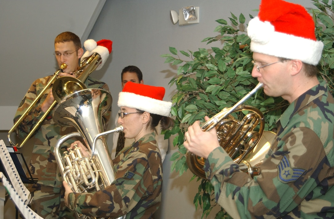 Staff Sgt. Matt Erickson (trombone), Senior Airman Meredith Healy (euphonium) and Staff Sgt. Ryan Heseltine (horn) perform holiday music during a stop at the 341st Mission Support and Comptroller Squadrons at Malmstrom Air Force Base. This group was one of seven ensembles from the USAF Heartland of America Band that divided up to visit six Air Force bases in the midwest sharing the holiday spirit with military members and their families. (U.S. Air Force photo/2nd Lt. Korry Leverett)