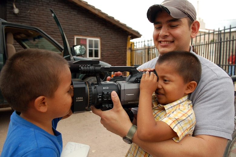 COMAYAGUA, Honduras – Army Sgt. William Nash, Armed Forces Network Honduras, shows two Honduran boys the camera he uses to do his job as a videographer.  Servicemembers from U.S. Southern Command and Joint Task Force-Bravo delivered more than 130 pairs of shoes to Hogar de Niños Tierra Santa orphanage here Dec. 8.  (U.S. Air Force photo by Staff Sgt. Austin M. May)
