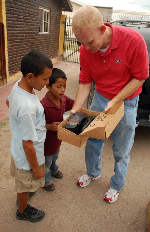 COMAYAGUA, Honduras – Air Force Chaplain (Capt.) Chad Bellamy, Joint Task Force-Bravo chaplain, admires a young Honduran boy's new pair of shoes, a gift from U.S. Southern Command and JTF-Bravo.  Servicemembers from both commands delivered more than 130 pairs of shoes to Hogar de Niños Tierra Santa orphanage here Dec. 8.  (U.S. Air Force photo by Staff Sgt. Austin M. May)