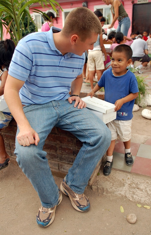 COMAYAGUA, Honduras – Air Force 1st Lt. Brian Robertson asks a young Honduran boy how he likes his new pair of shoes, a gift from U.S. Southern Command and Joint Task Force-Bravo.  Servicemembers from both commands delivered more than 130 pairs of shoes to Hogar de Niños Tierra Santa orphanage here Dec. 8.  (U.S. Air Force photo by Staff Sgt. Austin M. May)