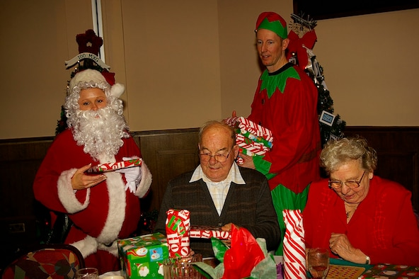 Santa and an elf helper give out presents to Charles and Kathleen Workman between bingo games. Members of the Top 3 Fellowship, along with other base members, helped host the event. This is the 26th year the event has been held by the Top 3. (U.S. Air Force photo by Karen Abeyasekere)