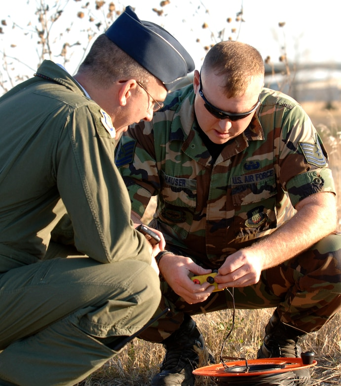 MCCONNELL AIR FORCE BASE, Kan. -- Col. Ray LaMarche, 22 Operation Group Commander, waits while Tech. Sgt. Phillip Hauser, 22nd Civil Engineer Squadron, prepares the triggering mechanism to detonate explosive ordinance behind the Combat Arms Range on Nov. 19. C-4 is used to detonate ordinance and it can be molded into any desired shape. (Photo by Airman 1st Class Roy Lynch III)