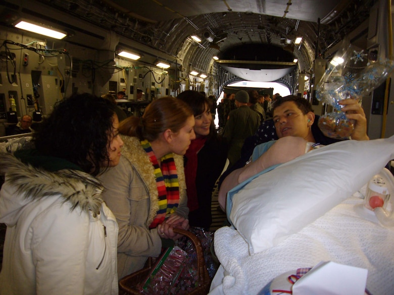 Paige Norris-Miller (left), Katie Jensen and Amy Smith, 37th Airlift Squadron bluetail spouses, deliver home-baked cookies to Tech. Sgt. Adam Popp Dec. 11 on board a C-17 Globemaster at Ramstein. (U.S. Air Force photo by Capt. Erin Dorrance)