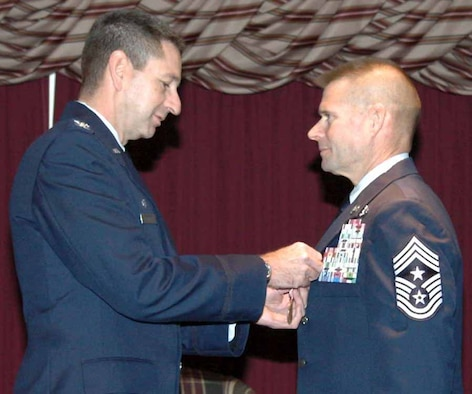 Col. Mark Correll, 72nd Air Base Wing and Tinker installation commander, pins a Meritorious Service Medal onto Chief Master Sgt. Phillip Cherry's lapel for his major accomplishments while stationed at Tinker. The 72nd ABW command chief master sergeant retired Dec. 10 after a 29-year career. (Air Force photo by Ralph Monson)