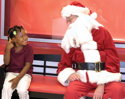 Mid-Del kindergartener Kyshaunna Broades shares a bench with Santa after shopping for new clothes with a B-52 Program Office volunteer during the annual Clothe-A-Kid event at JC Penney.  As Santa, Andy Jackson posed for photos with the children Dec. 6 and gave out candy canes and new backpacks filled with goodies. (Air Force photos by Margo Wright)