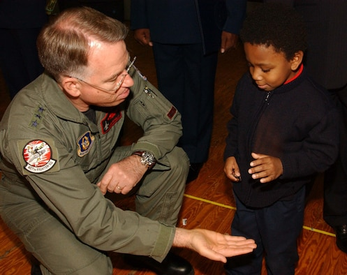 "ANDREWS AIR FORCE BASE, Md. -- Lt. Gen. John A. Bradley, commander of Air Force Reserve Command, gives a coin to the son of 459th Aeromedical Staging Squadron retiree Tech. Sgt. Gail Holley, in exchange for a playful ""gimme five"" at the 459th Air Refueling Wing commander's call Dec. 8. General Bradley attended the call to recognize star performers, chat with Airmen and discuss topics relevant to the AFRC. (U.S. Air Force photo/Staff Sgt. Amaani Lyle)"