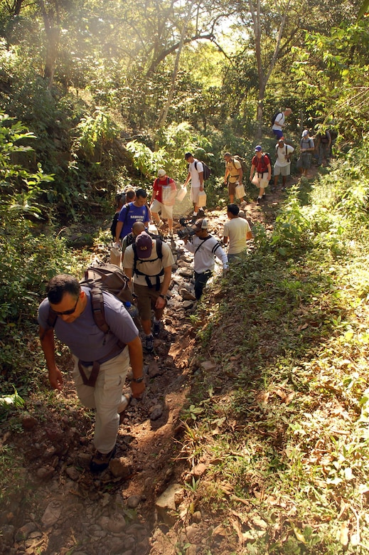 COMAYAGUA, Honduras -- Servicemembers assigned to Joint Task Force-Bravo cross a stream en route to the village of Capiro to deliver approximately 600 pounds of food Dec. 14.  The three-mile hike, sponsored by the JTF-Bravo chapel, was the fourth in a series of five scheduled trips.  (U.S. Air Force photo by Staff Sgt. Austin M. May)