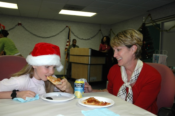 """Lt. Col. Rita Uribe, 325th Fighter Wing assistant staff judge advocate, eats dinner with her daughter Katie at the """"Hearts Apart"""" holiday party at the Airmen and Family Readiness Center here Dec. 13.  Colonel Uribe's husband, Lt. Col. Andy Uribe, Air Forces Northern chief of standerdization evaluation, is currently deployed as the 332nd Expeditonary Operations Group deputy commander.  (U.S. Air Force photo/Staff Sgt. Timothy R. Capling)"""