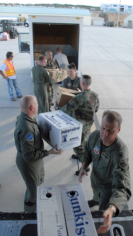 CURACAO, The Netherlands Antilles -- Aircrew from the 79th Rescue Squadron unloads boxes of cookies from an HC-130 here Dec. 12.  The ?Cookie Caper? morale mission allowed 12th Air Force leaders to visit with deployed servicemembers prior to the holidays. The team delivered more than 9,000 cookies to Honduras, the Netherlands Antilles, Puerto Rico, and Guantanamo Bay Naval Station, Cuba. (U.S. Air Force photo by Tech. Sgt. Sonny Cohrs)