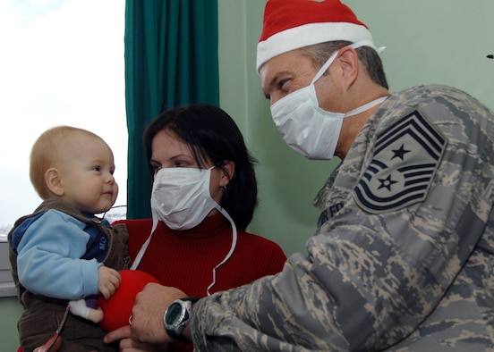 Chief Master Sgt. Martin Klukas, 3rd Air Force command chief, played Santa Claus by delivering Christmas presents to young patients in a Sarajevo children's hospital Dec. 17.  The chief's presence was part of a large 3rd Air Force effort. The unit collected and delivered Christmas gifts to more than 120 children. (Photo by Senior Master Sgt. Hollis Dawson)