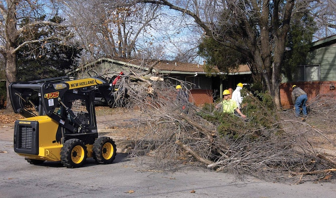 """A crew from Fryars Lawn Care and Landscaping moves down Doolittle in base housing this week, clearing yards of tree limbs.  Owner John Fryar says Tinker was hit """"pretty hard"""" and says after the initial clearing, crews will focus on pruning trees, removing broken branches still in the trees.  Other companies and crews are working across base to clean up after the ice storm."""