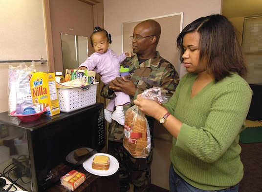 The ice storm left the Ledfords in a dark, cold home Dec. 9 but Tinker opened dorm rooms to them and other displaced Tinker families.  Staff Sgt. Timothy Ledford, 552nd Operations Support Squadron, his wife, Denise and their 18-month-old daughter Brianna make a sandwich in the small space, grateful for the free, safe accommodations. Smiling and appreciative, Sergeant Ledford still hopes his family will be able to return home before he deploys shortly after Christmas.  (Air Force photo by Margo Wright)