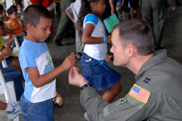 Capt. Patrick Dube, an aircraft commander with the 9th Special Operations Squadron, hands a Honduran orphan a candycane at Aldea Infantil S.O.S Orphanage in La Ceiba, Honduras during Operation Christmas Wish Dec. 13. Captain Dube was part of a 16 person team that helped deliver more than 875 Christmas packages to five different Honduran orphanages. (U.S. Air Force photo/Senior Airman Ali Flisek)