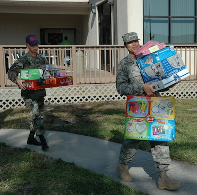 "Master Sgt. Phuoc Phan and Senior Airman Harmony Cook carry armloads of toys to waiting cars. Patrick's 1st Sergeants Association made the holiday season brighter for more than 300 foster children throughout Brevard County. ""Over the course of the past six years, they have donated more than 6,000 gifts,"" said Dr. Patricia Nellius-Guthrie, CEO of Community Based Care of Brevard. ""We are honored by their dedication and commitment to the community."" (U.S. Air Force photo by Airman David Dobrydney)"