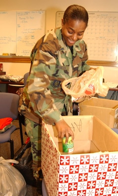 ANDREWS AIR FORCE BASE, Md. -- 1st Lt. Lavonne Johnson, 459th Air Refueling Wing Military Equal Opportunity chief, loads canned goods donated by wing members for the Holiday Food and Gift Drive Dec. 12. Lieutenant Johnson worked with the Human Resources Development Council here to assist a women and children's shelter in Charles County, Md., with money, food and supplies. (U.S. Air Force photo/Staff Sgt. Amaani Lyle)