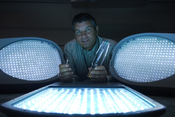 VANDENBERG AIR FORCE BASE, Calif. -- Scott Bly, 30 Civil Engineering Squadron, poses with regular light bulbs and Light Emitting Diode lights during the testing of several lights on Oct. 23. The test was conducted to determine which street light works better to save millions of dollars in energy cost base wide.  (U.S. Air Force photo/Airman 1st Class Ashley Tyler)