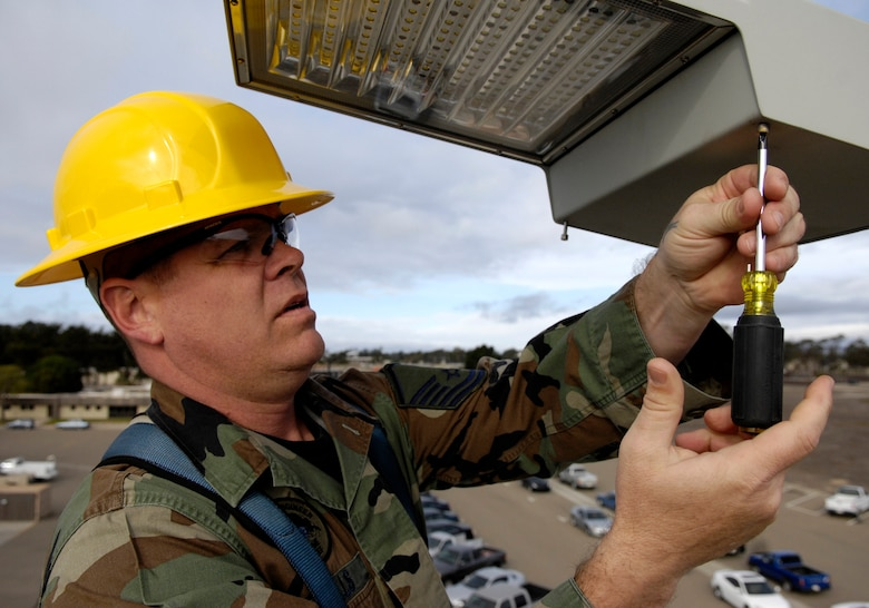 VANDENBERG AIR FORCE BASE, Calif. -- Master Sgt. Russell Wells, 30th Civil Engineering Squadron, inspects a Light Emitting Diode in front of the CES Operations Flight Building on Dec. 17. LED lights are being tested on Vandenberg to possibly replace current sodium vapor lamps. LED lights use three times less energy than sodium vapor lamps. (U.S. Air Force photo/Airman 1st Class Jonathan Olds)