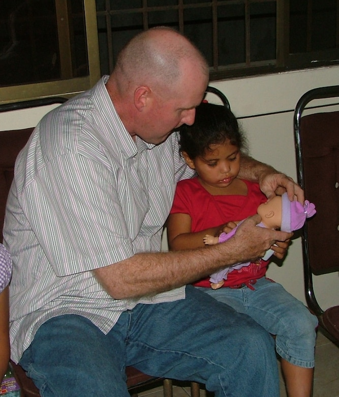 Senior Master Sgt. Clayton French, 478th Expeditionary Operations Squadron first sergeant, helps a girl at Shekinah Orphanage in Manta, Ecuador with her new toy.  The toys were given out as part of the FOL Manta's Toys for Tots program.  (U.S. Air Force photo/1st Lt. Malinda Singleton)