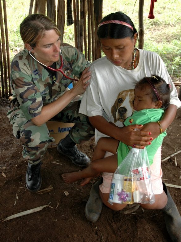 PIEDRA MESA, Costa Rica – Air Force Capt. Michelle Sredinski, Joint Task Force-Bravo Medical Element, listens to the breathing of a native Costa Rican woman at a makeshift clinic here Dec. 19.  JTF-Bravo deployed 28 servicemembers from Soto Cano Air Base, Honduras to Costa Rica, at the invitation of the country's Ministry of Health, for the first Medical Readiness Training Exercise in more than three years.  (U.S. Army photo by Spc. Grant Vaught)