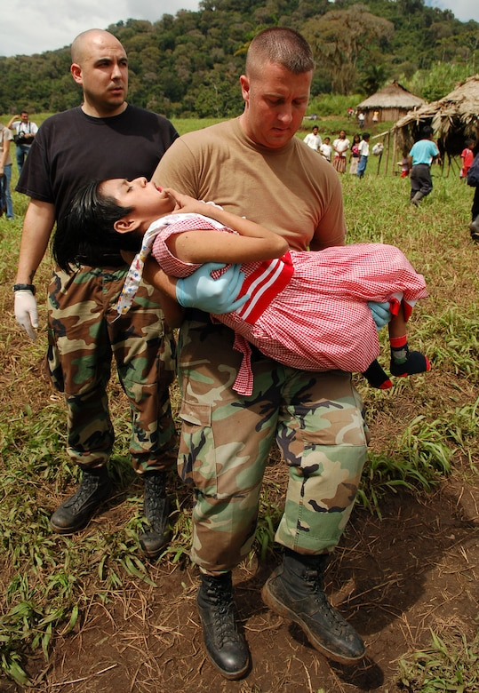 PIEDRA MESA, Costa Rica – Air Force Staff Sgts. Steven Geist (left) and David Pagani, Joint Task Force-Bravo Medical Element, take a young Costa Rican girl with cerebral palsy who has been diagnosed with pneumonia to a waiting helicopter to be air evacuated from a makeshift clinic to a hospital in Limon Dec. 18.  JTF-Bravo deployed 28 servicemembers from Soto Cano Air Base, Honduras to Costa Rica, at the invitation of the country's Ministry of Health, for the first Medical Readiness Training Exercise in more than three years.  (U.S. Air Force photo by Staff Sgt. Austin M. May)