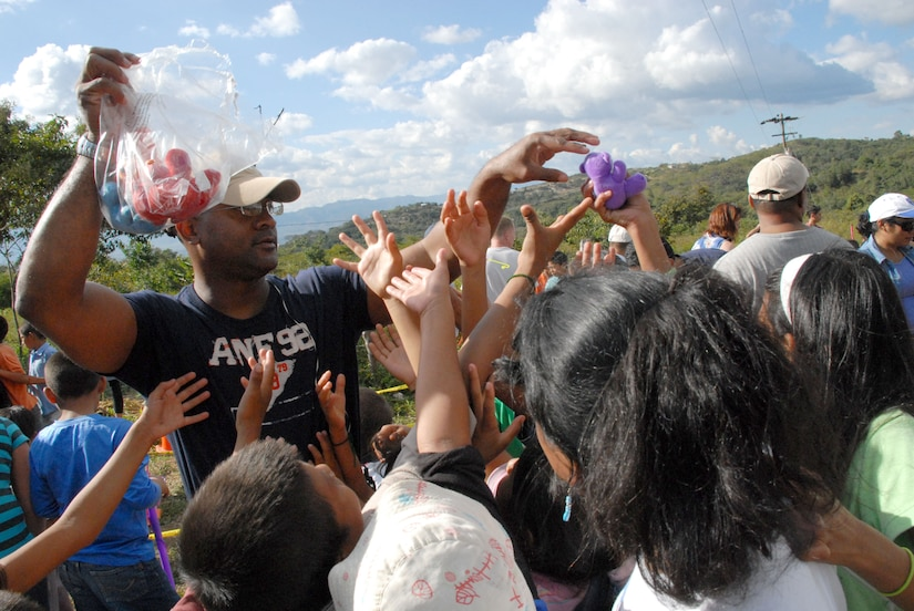 COMAYAGUA, Honduras -- Air Force Maj. Anthony Jacobs, the personnel director for Joint Task Force-Bravo, hands out stuffed animals to Honduran children here Dec. 23 during a toy giveaway. The toy drive was organized by the Joint Task Force-Bravo Chapel and the gifts were donated by the families of servicemembers stationed at Soto Cano Air Base, Honduras.  (U.S. Air Force photo by Tech. Sgt. Sonny Cohrs)
