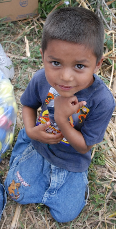 COMAYAGUA, Honduras - A young Honduran boy from a nearby village clutches his new toys he received from American Soldiers, Sailors and Airmen here Dec. 23.  A toy drive was organized by the Joint Task Force-Bravo Chapel and the gifts were donated by the families of servicemembers stationed at Soto Cano Air Base, Honduras.  (U.S. Air Force photo by Tech. Sgt. Sonny Cohrs)