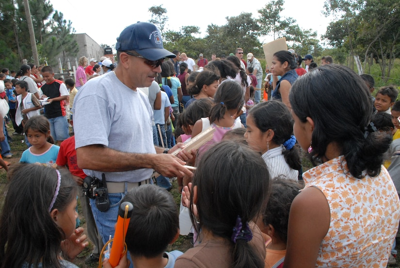 COMAYAGUA, Honduras - Herberth Gaekel, 612th Air Base Squadron fire inspector, hands out rulers to Honduran children waiting in line to receive toys from Joint Task Force-Bravo servicemembers here Dec. 23.  The toy drive was organized by the JTF-Bravo Chapel and the gifts were donated by the families of servicemembers stationed at Soto Cano Air Base, Honduras.  (U.S. Air Force photo by Tech. Sgt. Sonny Cohrs)