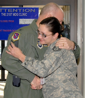 After an emotional moment, newly-promoted Tech. Sgt. Shannon Alequin hugs 21st Space Wing commander Col. Jay Raymond after being 'STEP' promoted Dec. 21. Known as 'Stripes for Exceptional Performers,' units use additional promotion slots to promote exceptional members in their organizations. Sergeant Alequin is assigned to the 21st Medical Support Squadron.  (U.S. Air Force photo/Roberta McDonald)
