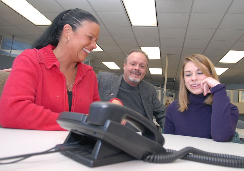 As Tech. Sgt. Christopher Harry talks through a long-distance phone line, his family and girlfriend listen in on Christmas Eve. From left to right are Sergeant Harry's mother, Susan; father, William, and girlfriend, Valerie Sicard. The three gathered at the Westover Public Affairs Office for a conference call with the 42nd Aerial Port Squadron Airman, who is deployed to Southwest Asia over the holidays. (photo by Don Treeger, Springfield, Mass., Republican newspaper)