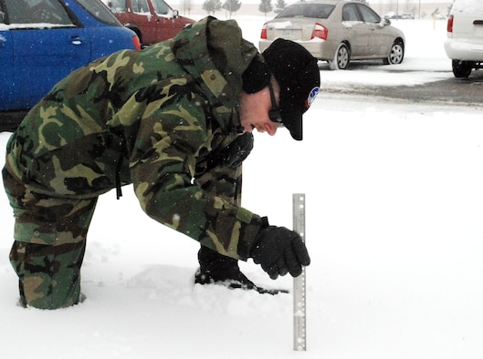 Tech. Sgt. Aaron Wesson, 90th Operations Support Squadron, measures the snow accumulation here Dec. 7. Warren had a total of six and a half inches of snow from Dec. 7 to 9 (U.S. Air Force photo by Staff Sgt. Chad Thompson).