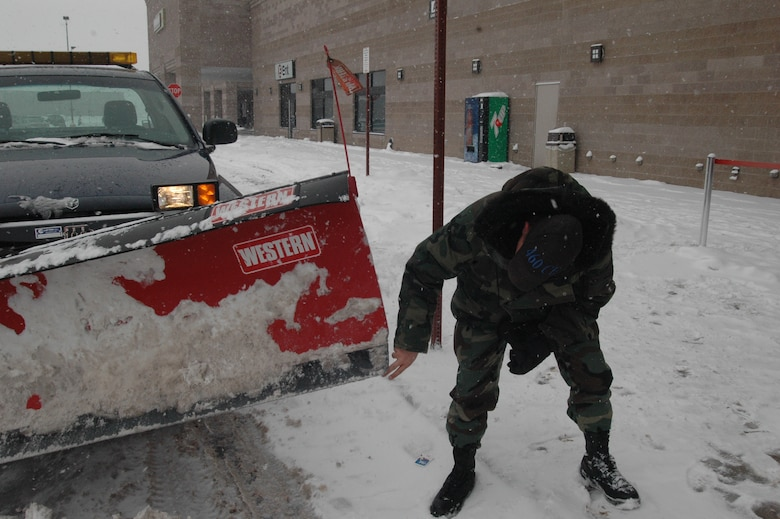 Tech. Sgt Jeffrey Dickson, from the 460th Civil Engineer Squadron, checks his blade for wear while plowing the parking lot at the Buckley Base Exchange and Commissary during a snowstorm Dec. 27.  When the blade wears down to shorter than two fingers, he will replace it. (U.S. Air Force photo by Capt. Adrianne Michele)