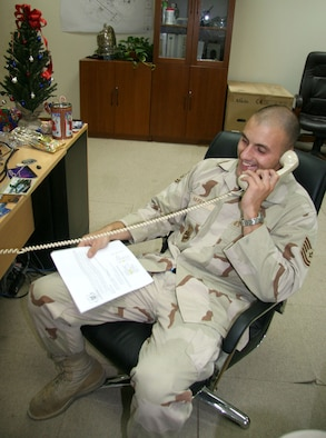 Tech. Sgt. Christopher Harry, deployed to Southwest Asia over the holidays, shares cheerful conversation on Christmas Eve during a conference call with his family. Sergeant Harry is an Air Force Reserve Command aerial port technician who has been deployed since September. (US Air Force photo/Master Sgt. Ruby Zarzyczny)