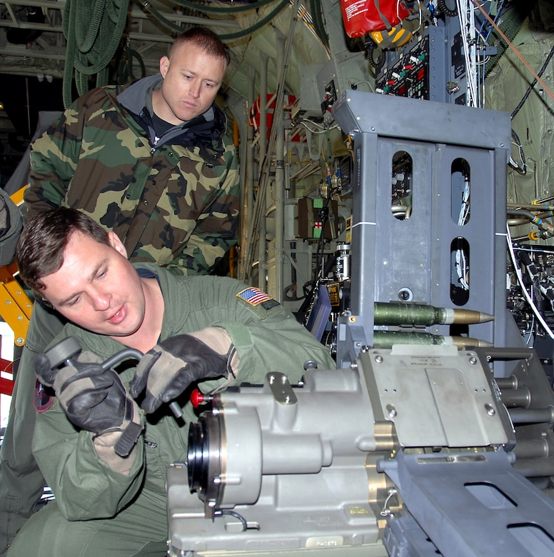 Tech. Sgt. Ben Filek works on a newly-installed 30 mm Bushmaster cannon aboard an AC-130U Spooky gunship as Tech. Sgt. James Knight looks on Jan. 26 at Hurlburt Field, Fla. Both Airmen are aerial gunners with the 19th Special Operations Squadron at Hurlburt Field. The 30 mm gun will eventually replace both the 40 mm cannon and 25 mm gun on U-model gunships. (U.S. Air Force photo/Chief Master Sgt. Gary Emery)
