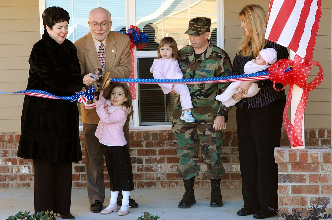 Kathryn Thompson, managing director of American Eagle Communities, helps Lowell Klepper, 23rd CES deputy base civil engineer and Brianna McKay, cut the ribbon on her family's new home Jan. 31. Brianna is the daughter of Tech. Sgt. Martin and Maria McKay. The family will be  moving into the three-bedroom 1,630 square-foot home as soon as community projects are completed.  (U.S. Air Force photo by Airman 1st Class Gina Chiaverotti)