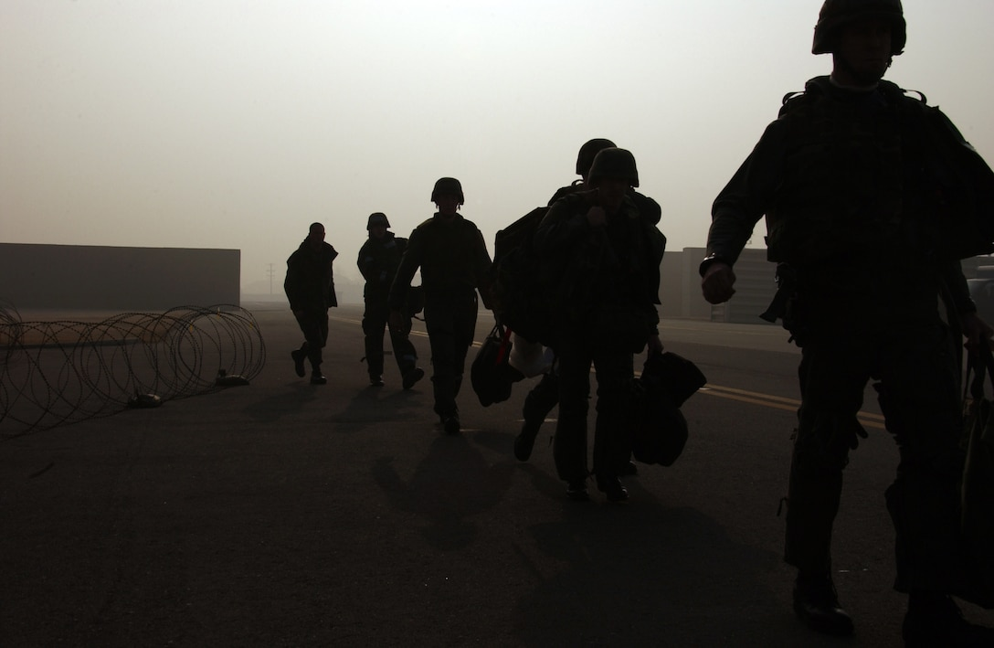 """OSAN AIR BASE, Republic of Korea --  Members of the 36th Fighter Squadron bug out to the 25th Fighter Squadron after an attack on Osan. The """"attack"""" left the building on fire. (U.S. Air Force photo by Airman 1st Class Chad Strohmeyer)"""