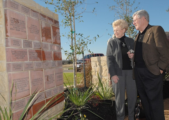 Lois and Fred Jones admire a wall of engraved bricks built at a gazebo between Lackland Air Force Base's Fisher House I and II. They are among brick donors who attended a Jan. 25 dedication of the wall. The donors helped pay Fisher House operating expenses from 1999 to 2005. (USAF photo by Robbin Cresswell)