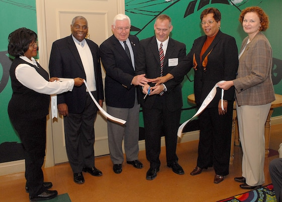 Frank Falkstein (third from right) cuts a ribbon, with assistance from retired Maj. Gen. Tom Hickey and Maryland Jones, in Lackland's Fisher House III on Jan. 25. The ceremony was to dedicate a wall built of engraved bricks from donors who provided Fisher House operating expenses from 1999 to 2005. Mr. Falkstein is from David Weekley Homes, which built the wall. General Hickey is Fisher House board president, and Ms. Jones is director of volunteer services at Wilford Hall Medical Center at Lackland Air Force Base, Texas. The donors help keep Fisher House a free home-away-from-home for visiting families of hospital patients. Also shown, from left, are Ramona Lewis, Fisher House Executive Director Ray Holmes and Andrea Menard. Mr. Holmes presented plaques to Mr. Falkstein and Col. Eric Wilbur, vice commander of the 37th Training Wing at Lackland AFB, honoring their organizations' assistance to Fisher House. (USAF photo by Robbin Cresswell)
