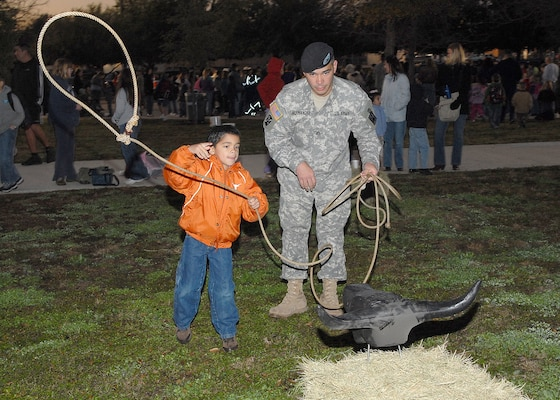 """Jacob Hernandez, 6, a kindergarten student at Lackland Elementary School, tries to lasso a makeshift bull Jan. 26 during the 3rd Annual Lackland Independent School District Cowboy Breakfast. Encouraging his son is Army Staff Sgt. Jacob Hernandez, an analyst in Lackland's 314th Military Intelligence Battalion. The breakfast was """"a rip-roaring success,"""" attracting its largest crowd yet, about 460 students, parents and teachers, said the coordinator, Librarian Robbye Durham. She said students learn about Texas' ranching history in the week preceding the breakfast, held the same morning as the city's annual Cowboy Breakfast kickoff for the San Antonio Stock Show & Rodeo. (USAF photo by Robbin Cresswell)"""