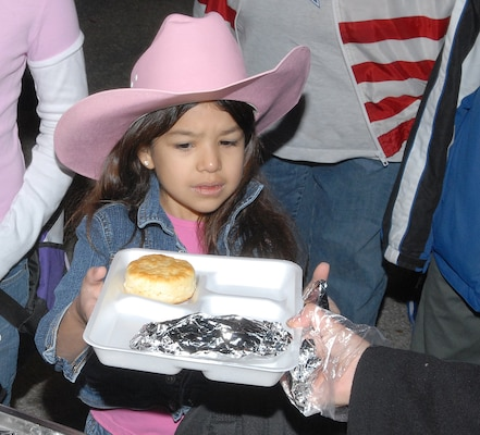 Laura Gutierrez, 6, a Lackland Elementary School first-grader, is handed an egg, potato and cheese taco and a biscuit Jan. 26 during the 3rd Annual Lackland Independent School District Cowboy Breakfast. She is the daughter of Amanda and Staff Sgt. Victor Gutierrez of the Cryptologic Systems Group. Breakfast-goers chowed down on 500 tacos containing 45-dozen eggs, 500 biscuits, 350 servings of grits, hot chocolate, coffee and a variety of fruit juices. (USAF photo by Robbin Cresswell)