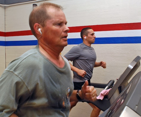 Lt. Col. Kurt Austin, Air Force Operational Test and Evaluation Center, and 1st Lt. Robert Lady, Space Development and Test Wing, run on tread mills at a fitness center here. (U.S. Air Force photo by Todd Berenger)