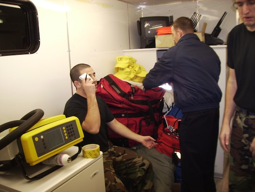 Ryan Burke, 341st Civil Engineer Squadron fire department member, checks the vital signs of Senior Airman Zalman Kosofsky before he suits up and enters the incident site on the Blackfeet Indian Reservation in Browning, Mont., Jan. 24. Team Malmstrom personnel were responding to a report of a suspicious package found in the Tribal Offices there.