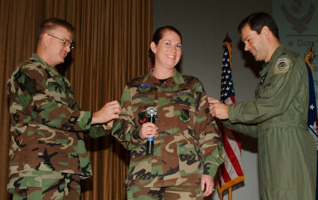 Tech. Sgt. Julie Morris, 16th Electronic Warfare Squadron, gets her new master sergeant stripes tacked on by Chief Master Sgt. Randy Salefske, 53rd Wing command chief, and Col. Ken Wilsbach, wing commander, at a commander?s call Dec. 21.